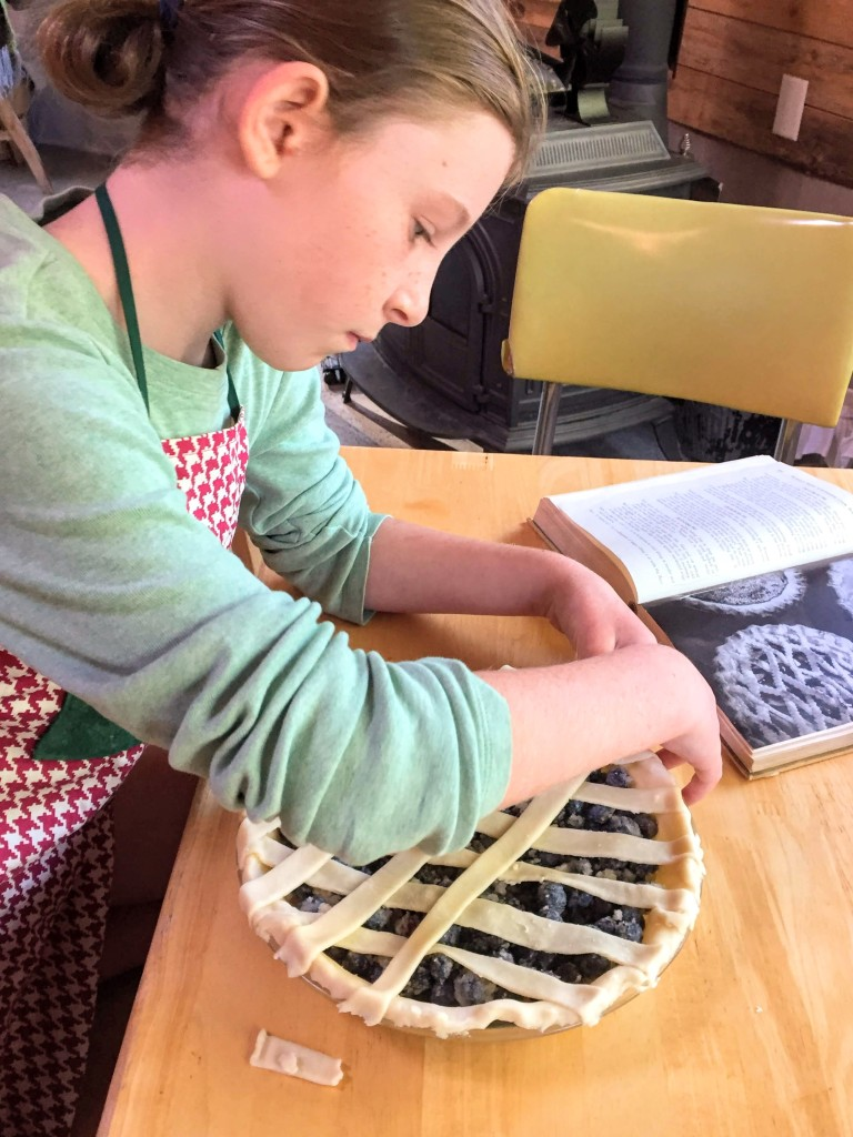 Child making blueberry pie from scratch.